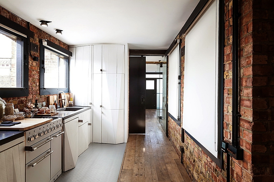 Spacious-modern-kitchen-with-exposed-brick-walls-linking-the-reception-and-the-bedroom