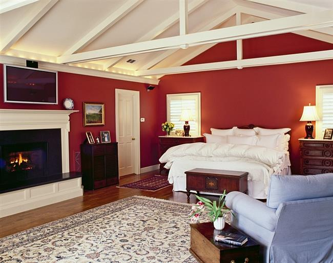 Просторная спальня с яркими красными стенами.