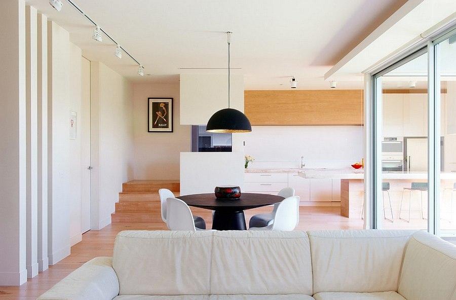 Небольшая семейная зона отдыха, визуально отделенная от обеденной зоны одним только белым кожаным диваном.