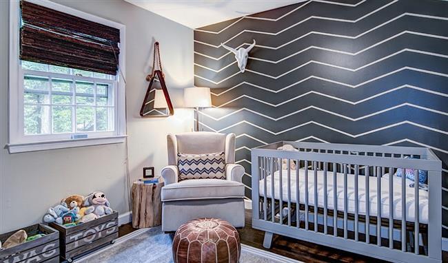 Детская комната с серой стенкой, украшенной угловатыми белыми полосами.