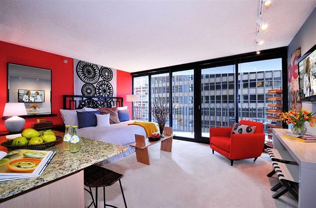 Красная стена и мягкое кресло в интерьере спальни.