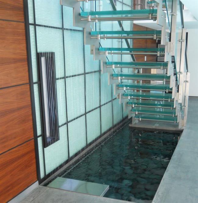 Стильная лестница с прудом и водопадом в роскошном особняке.