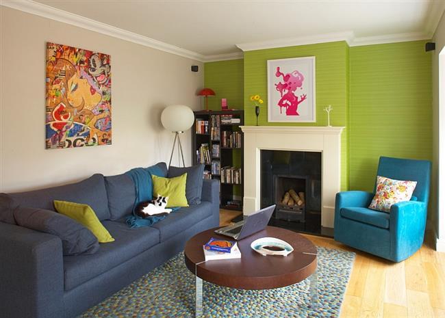 Стильная гостиная с однотонными зелеными обоями.