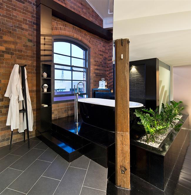 Индустриальная комната со стильной черно-белой ванной на помосте.