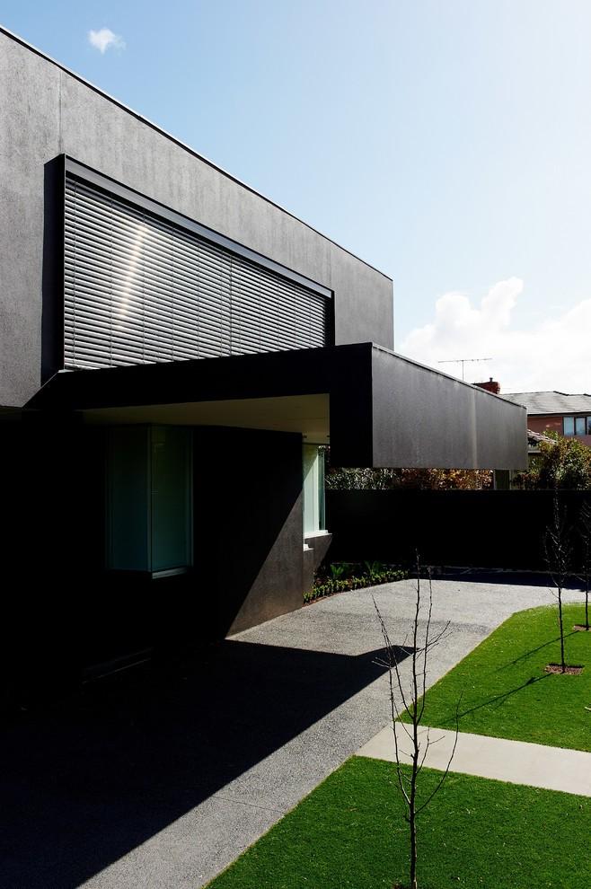 Черный внешний фасад дома с современным навесом, который закрывает вход в гараж.