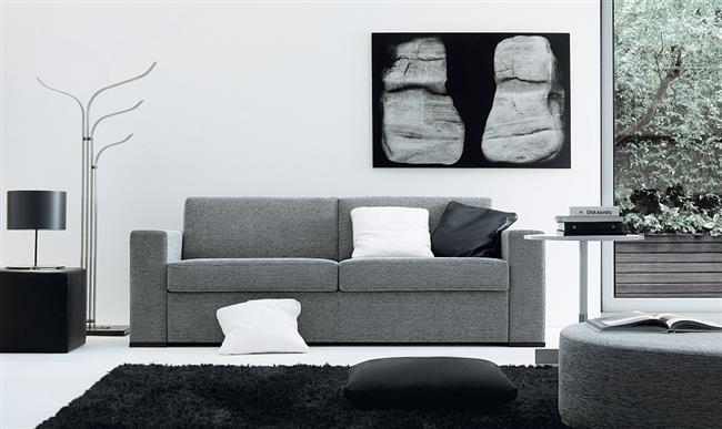 Стильный серый диван в черно-белой гостиной.