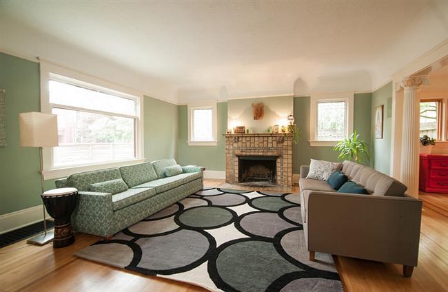 Просторная зеленая гостиная в минималистическом стиле.