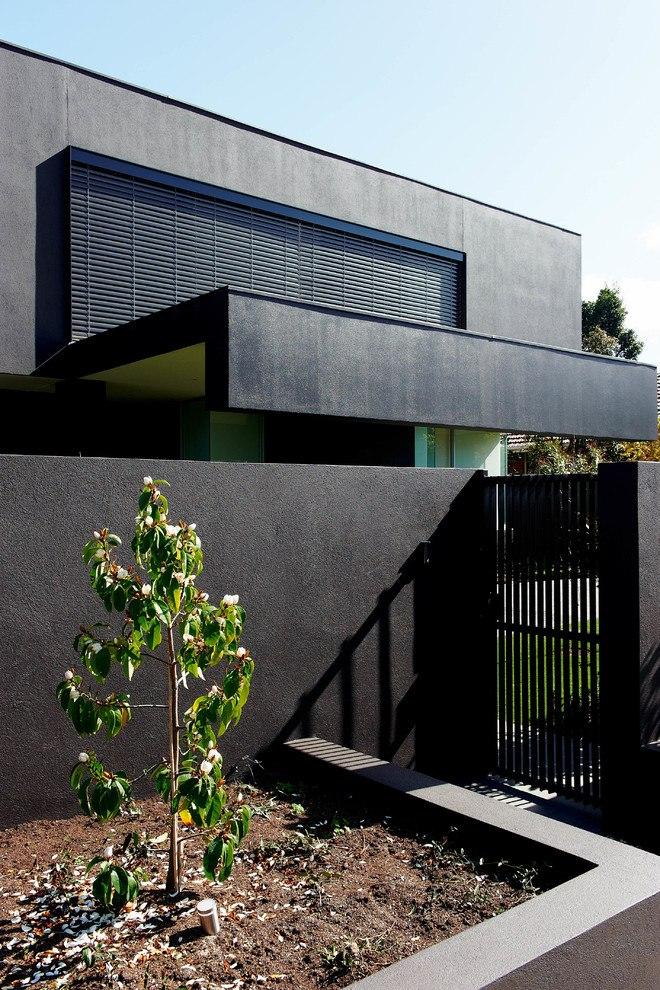 Фасад дома скрывается за массивным черным забором, в котором находится небольшая решетчатая калитка для входа жильцов дома.