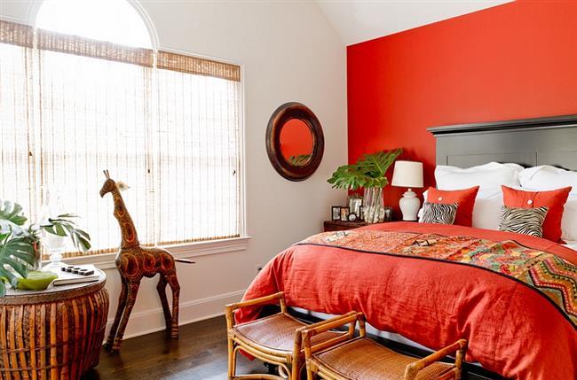 Небольшая спальня в красно-оранжевых тонах.