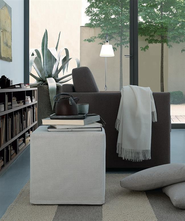 Стильный коричневый диван в светло-серой гостиной.