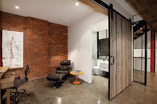 Индустриальный офис с раздвижной деревянной дверью.