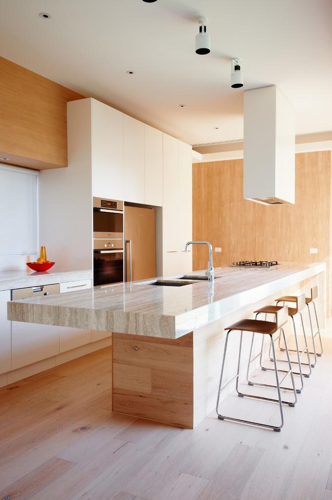 Пол, стены и мебель в кухонной зоне отделаны светлой древесиной.