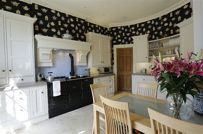 Кухня в классическом стиле с необычными узорчатыми обоями.