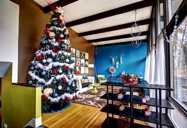 Яркая пушистая елка в современной стильной гостиной.