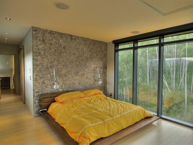 Уютная, элегантная спальня первого этажа с видами на лес.