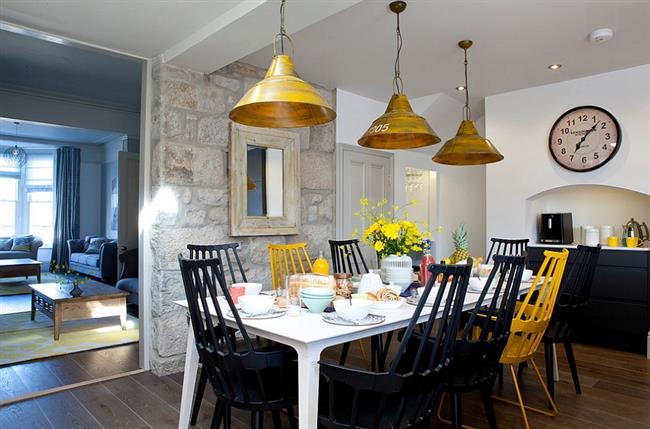 Стильная столовая с черными и желтыми стульями.
