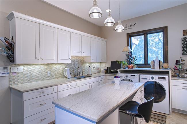 Стильная прачечная, объединенная с кухней и домашним кабинетом.