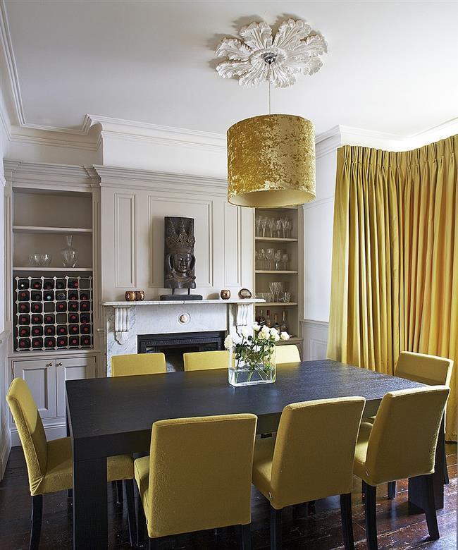Подвесной светильник, стулья и портьеры желтого цвета в интерьере столовой.