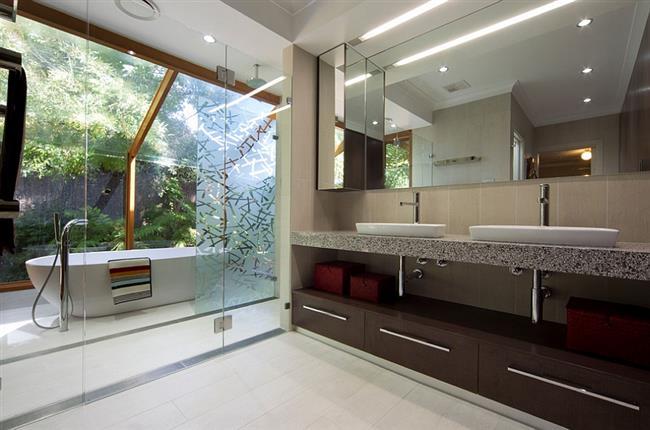Уличная ванная комната под стеклянным навесом.
