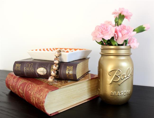 Позолоченная ваза с живыми цветами для украшения гостиной.