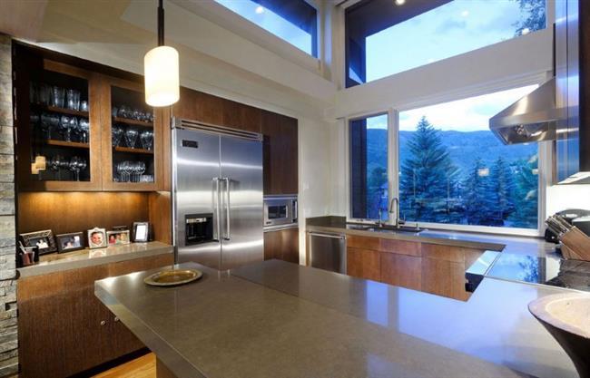 Современная кухонная зона с видами на лес и горы.