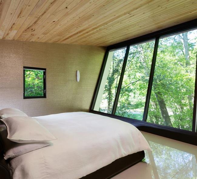 Небольшая спальня в минималистическом стиле с видами на лес.