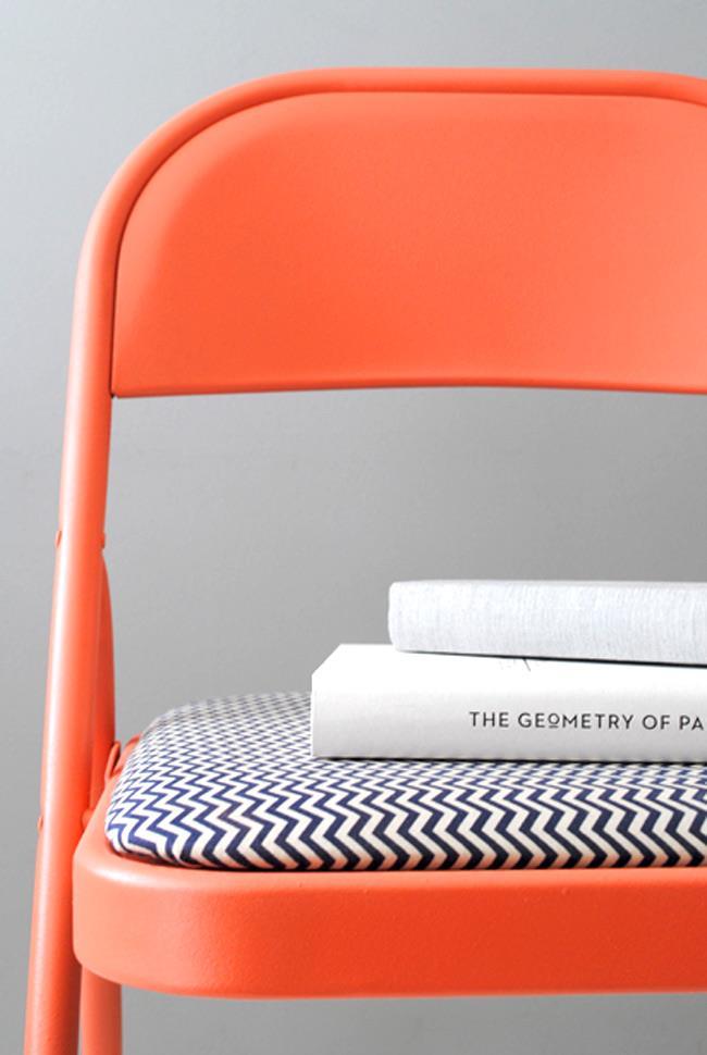 Складной стул в ярких оттенках оранжевого цвета.