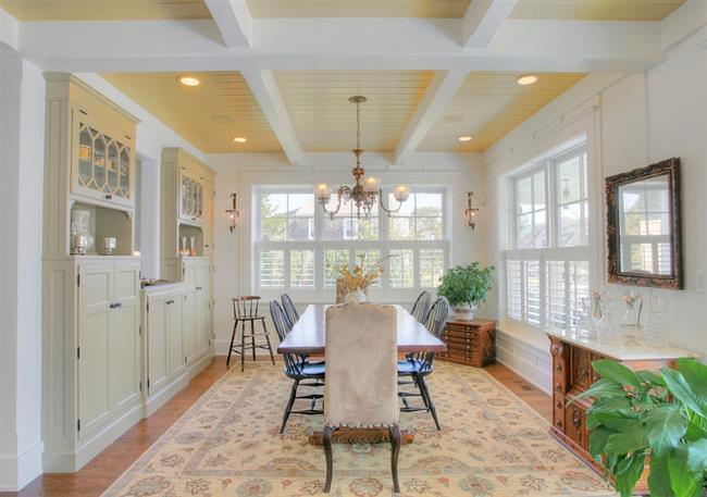 Уютная столовая с желтым потолком и напольным покрытием.