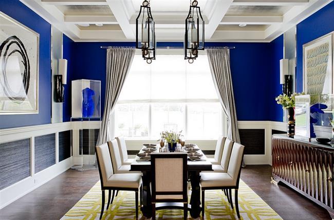 Яркая столовая в синих тонах с желтым узорчатым ковриком.