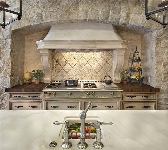 Полукруглая вытяжка и изогнутые краны в интерьере кухни.