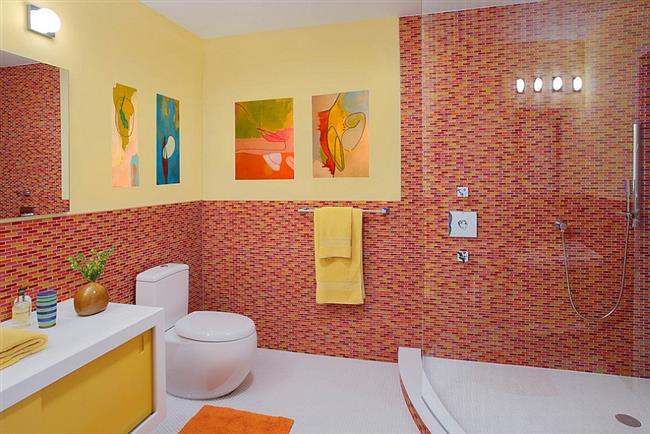 Ванная комната с красной и желтой плиткой на стенках.