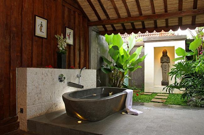 Каменная ванная под большим деревянным навесом.