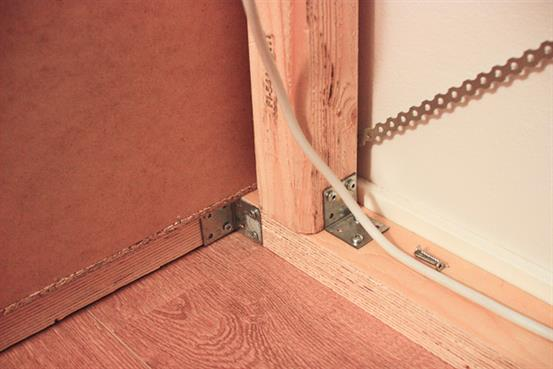 Металлические скобы, скрепляющие шкафы кровати.