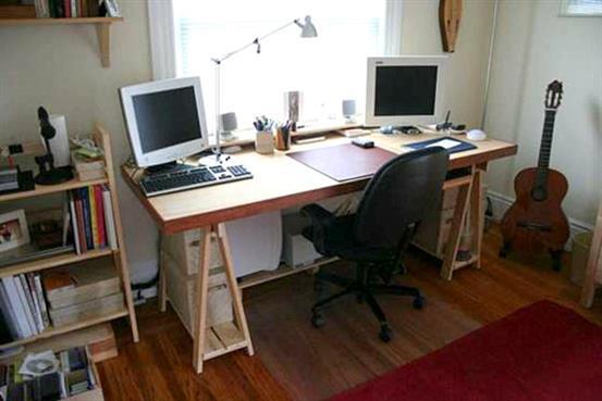 Удобный рабочий стол из двери и деревянных стоек.