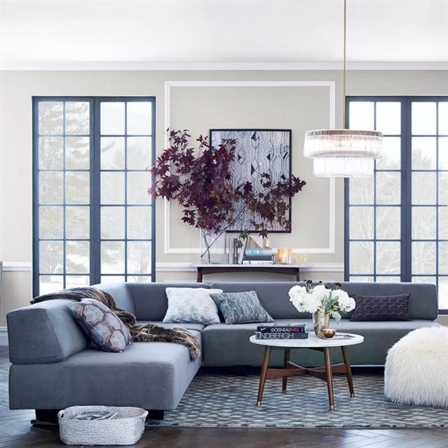 Элегантный диван светло-серого цвета в просторной гостиной.
