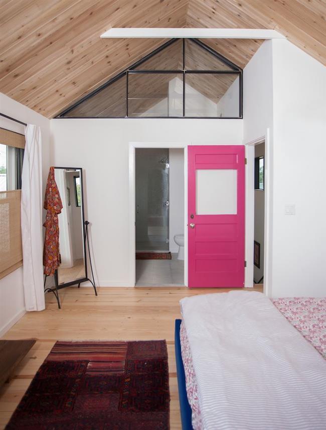 Яркая розовая межкомнатная дверь в интерьере спальни.