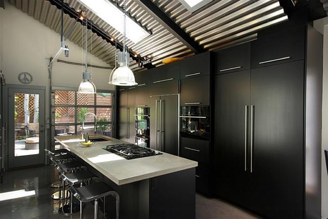 Стильная кухня в темных тонах с мансардными окнами.