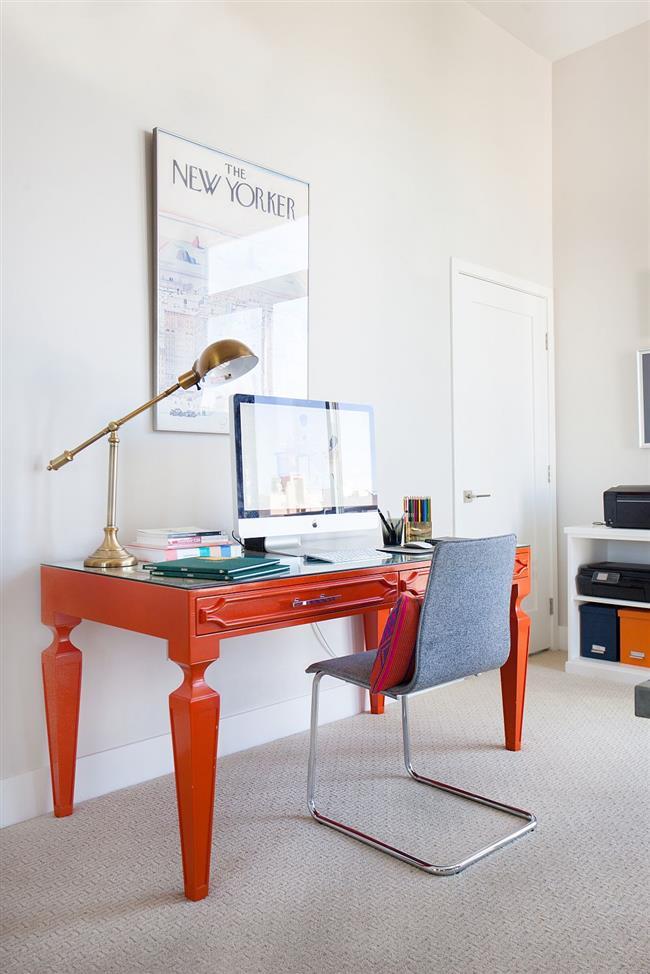Яркий оранжевый стол в современном кабинете.