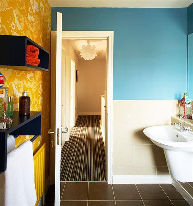 Небольшая уютная ванная с голубыми и желтыми стенами.