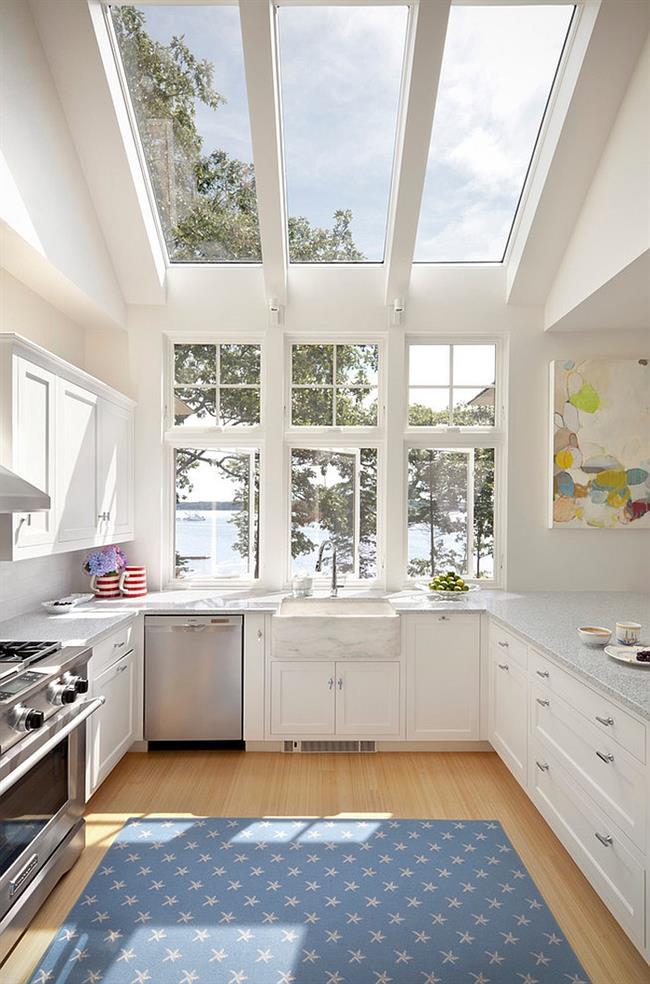 Белая кухня с большими мансардными окнами.