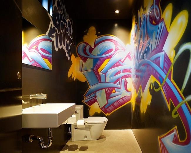 Ванная комната с черными стенами и граффити.