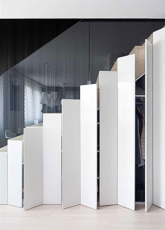 Просторная гардеробная, оборудованная под лестницей квартиры.