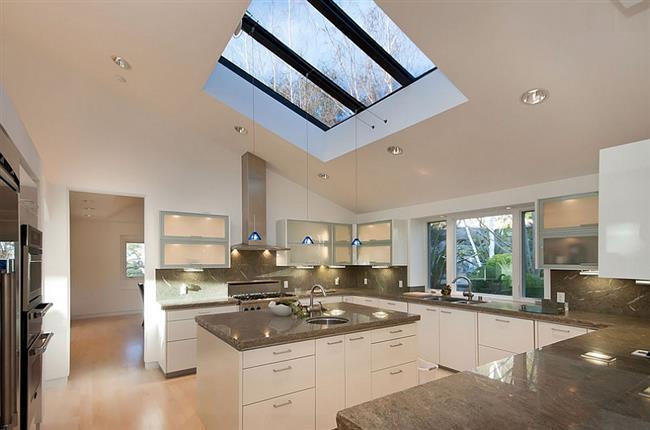 Современная кухня с мансардными окнами черного цвета.