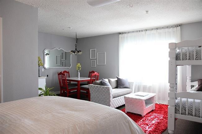 Эклектическая спальня с красными аксессуарами и мебелью.