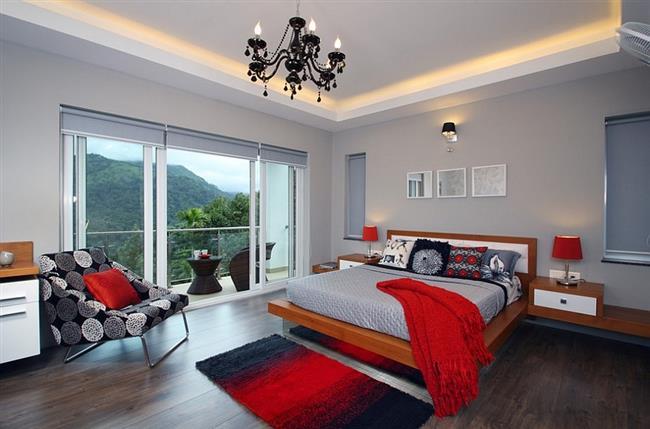 Серая спальня с элементами яркого красного цвета.