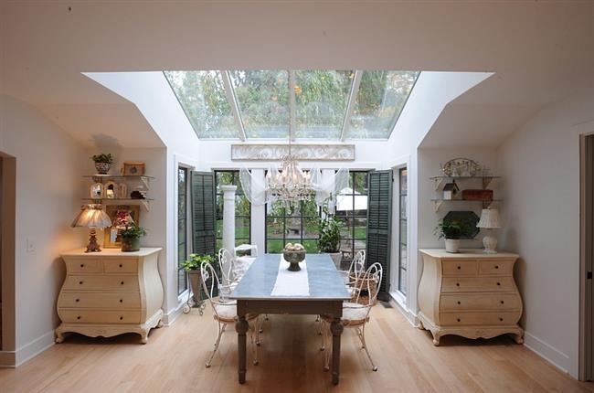 Небольшая столовая с панорамными и мансардными окнами.