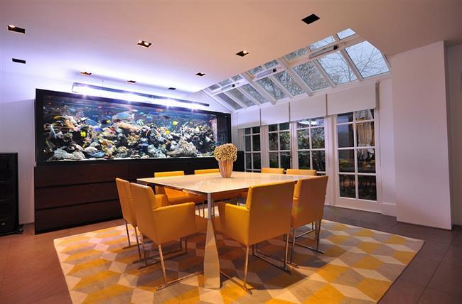 Необычная столовая с мансардными окнами и аквариумом.
