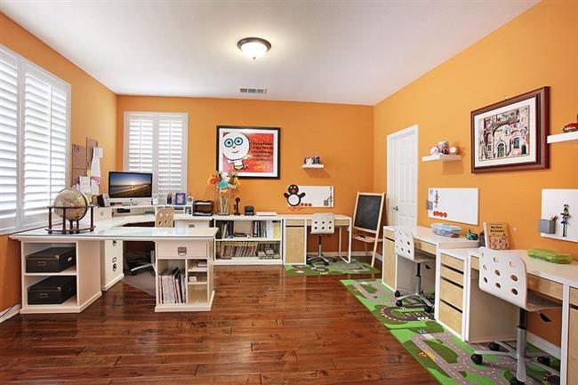 Яркий необычный домашний кабинет с оранжевыми стенами.