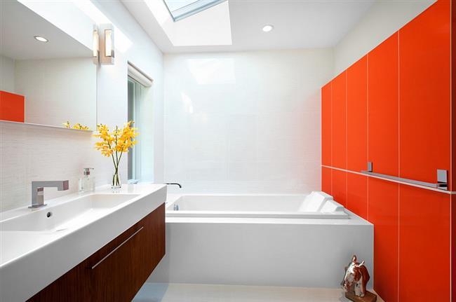 Небольшая ванная в белых и оранжевых тонах.