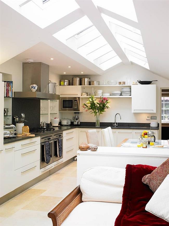 Стильная кухня в белых тонах со скошенным потолком.